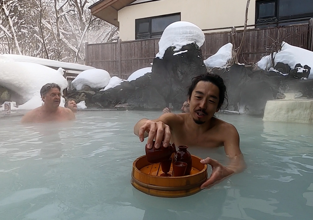 Our tail guide Taro pouring a sake in a Hachimantai onsen